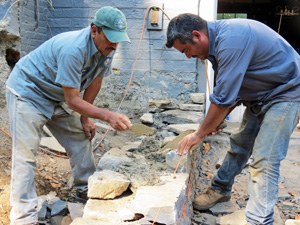 Foreman Federico Antonio and Juan Dominguez of Millbrook Gardens Landscaping and Garden Center work on the construction of a rock wall.