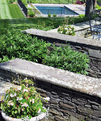 Intricate stone walls with accompanying plantings leading down to a landscaped pool area.