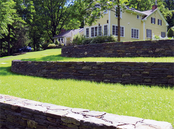 Stone walls and lawns leading up a hill to the home.